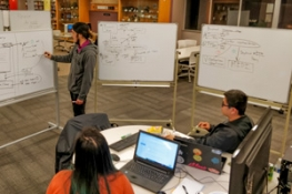 students using a whiteboard at the Hackathon